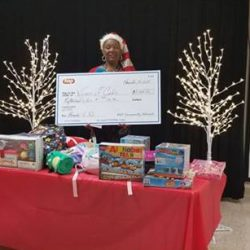 Evelyn McGovern Holds a check at the 5th Annual Warm a Child for Winter Event